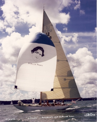 Earl McMillen's smiling face graced Onawa (US-6's) spinnaker while sailing at the America's Cup Jubilee, Cowes England, 2001; Earl himself stands below on the foredeck.